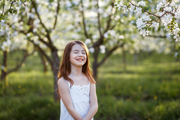 A portrait of a beautiful young girl with her eyes closed  in a white dress in the garden with apple trees blosoming having fun and enjoying smell of flowering spring garden at the sunset