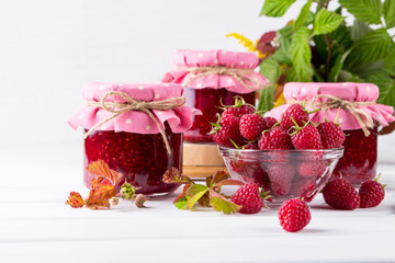 Preserved berry. Glass jar with homemade raspberry jam on a white background.