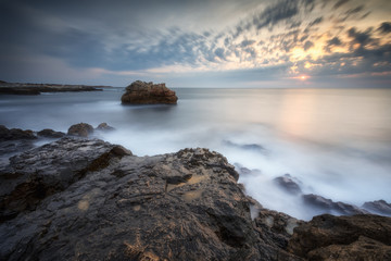 Amazing sea sunrise with slow shutter and waves flowing out.