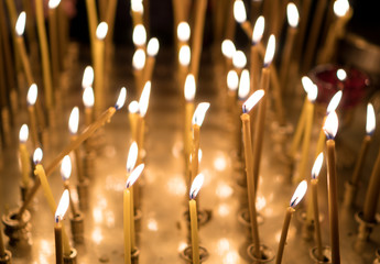 Many candles glowing on table in the church.