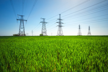 High voltage lines and power pylons in a green agricultural landscape with blue sky on a sunny day.