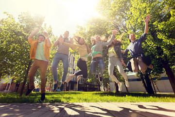 friendship, motion, action, freedom and people concept - group of happy teenage students or friends jumping outdoors