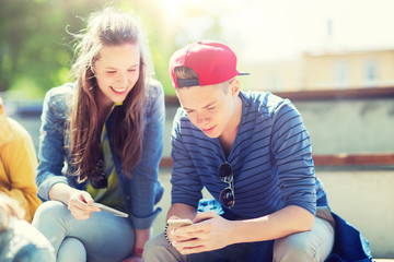 technology, internet and people concept - happy teenage friends with smartphones outdoors