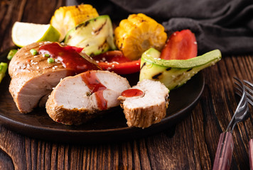 Chicken fillet with sauce and grilled vegetables on a wooden background.