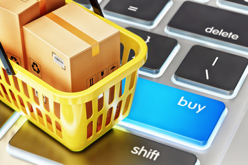 Online shopping, internet purchases and e-commerce concept, yellow shopping basket with cardboard boxes on computer keyboard with blue buy button