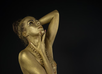 woman fully dressed in gold  on black background