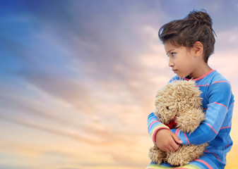 childhood, sadness, loneliness and people concept - sad little girl with teddy bear toy over evening sky background