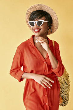 Studio portrait of beautiful young black smiling woman with short brown hair, red lips, dressed in orange red dress, white sunglasses, hat, with net bag