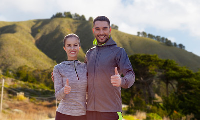 fitness, sport and gesture concept - smiling couple outdoors showing thumbs up over big sur hills background in california