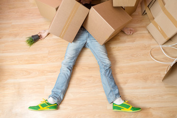 Photo of man in jeans and sneakers lying under cardboard boxes