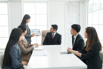 A confident business team of mixed ages and ethnicity are holding a meeting in a modern office. They are discussing ideas for their business development.