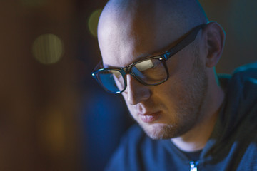 cybercrime, hacking and people concept - close up of bald hacker in glasses