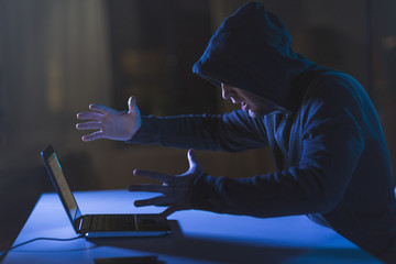 cybercrime, hacking and technology crime - angry male hacker with laptop computer in dark room