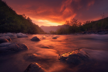 fast mountain river flowing In sunset time