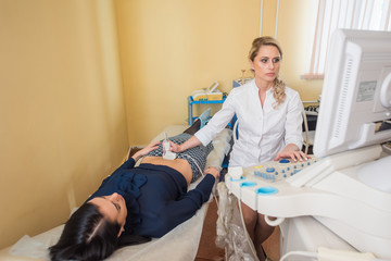 Ultrasound test. Pregnancy. Gynecologist checking fetal life with scanner.