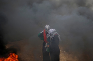 Female Palestinian demonstrators stand amidst smoke during a protest demanding the right to return to their homeland, at the Israel-Gaza border, east of Gaza City
