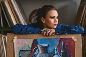 Young beautiful girl, female artist painter thinking of a new artwork idea or project holding a finished picture artwork depicting still life in blue and red colors