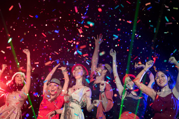 In selective focus of Cheerful young people showered with throwing confetti on a club party.Festival Event Party with People concept.Clubber drinking.