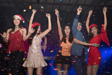 ancing in club.Cheering crowd young people at New Year - holiday celebration background.