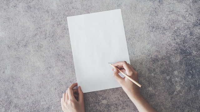 Hand writing on blank paper with pencil