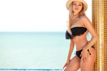 Beautiful fit woman in black swim suit and hat posing on the beach. Summer vacation.