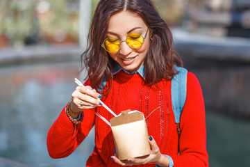 Asian Woman eating street food from takeaway paper box outdoors in Hong Kong