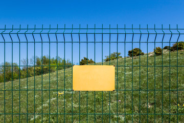 A blank sign on a dangerous zone or forest reserve. Closed area, fenced with metallic green mesh and yellow warning plate.