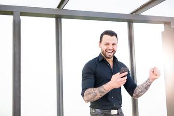 Junger erfolgreicher Geschäftsmann und Startup lacht und jubelt glücklich mit Smartphone in der Hand und telefoniert.