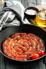Barbecue sausages in frying pan on wooden table.