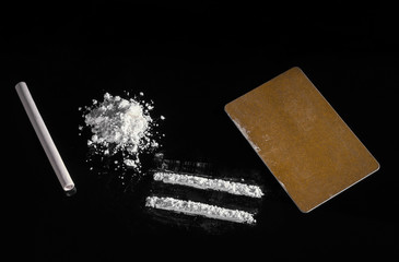 white powder is scattered on a black background with a slide, strips are made with a golden color card and a tube that is inhaled