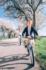 Father with son ride a bicycles on country road under the blossom trees at spring time