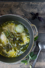 homemade chicken broth with onions and fresh herbs in rustic setting
