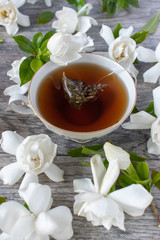 relaxing china cup of tea surrounded by gardenia blossoms