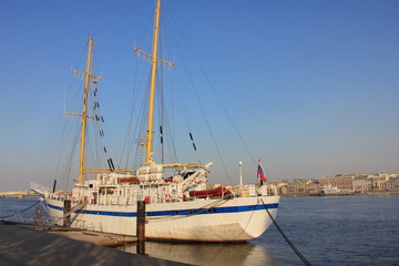 Sail Boat Moored on Water and Tied to Pier. Luxury White Ship on Waterfront Embankment in St Petersburg, Russia. Vintage Yacht or Cruise Ship at Marina Lot before Sunset with Empty Sky Background.