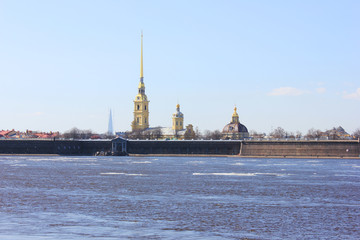 Peter and Paul Fortress in Saint Petersburg City, Russia. Scenic Outdoors View of Popular Tourist Landmark with Neva River Water with melting Ice and Sky Background on Sunny Spring Day Landscape.