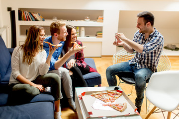 Young friends eating pizza at home and having fun