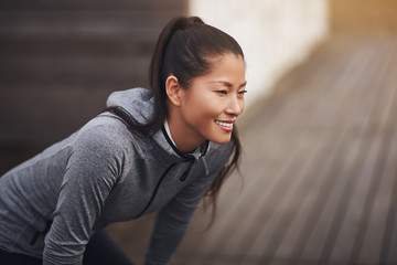 Young Asian woman in sportswear preparing to go jogging