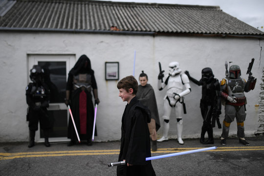 A boy with a light saber walks past a group of Star Wars fans dressed in costumes during the inaugural 'May The 4th Be With You' festival in the County Kerry village of Portmagee