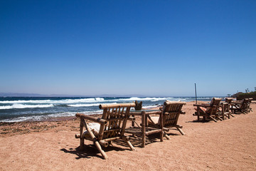 Row of bamboo chaise lounge on beach in Dahab, Sinai, Egypt. Beautiful seascape. Relax time.