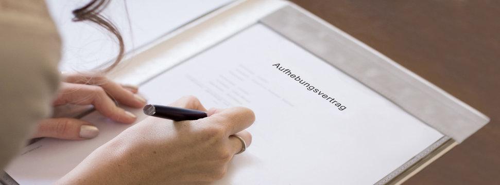 junge Frau unterzeichnet Aufhebungsvertrag
