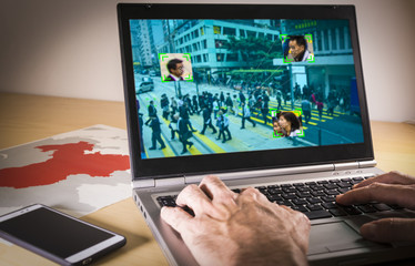 Laptop with street image and facial recognition over a table with a map of China. China has announced plans for widespread facial recognition camera coverage in cities and homes by 2020