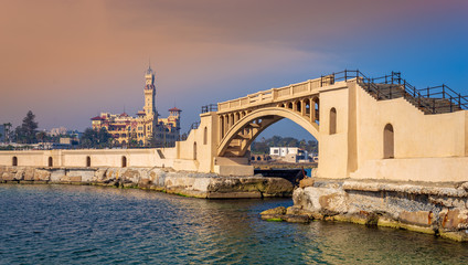 Bridge in the sea at the tea island of Montazah park and the Royal palace in the far distance with calm sea at sunrise time, Alexandria, Egypt