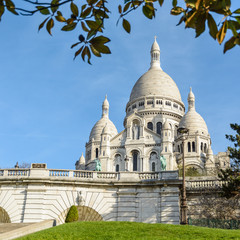 The bright white basilica of the Sacred Heart of Paris, situated at the top of the Montmartre hill, seen from the Louise Michel park by a sunny spring morning with foliage in the foreground.