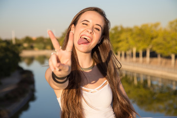 Happy young woman standing in park on sunny day and gesturing victory.