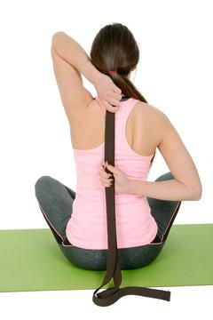 Young woman doing yoga using belt like props