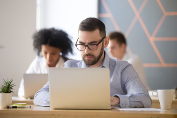 Serious businessman in glasses focused on computer work in coworking office, concentrated millennial manager, developer or programmer solving problem using business software on laptop at workplace