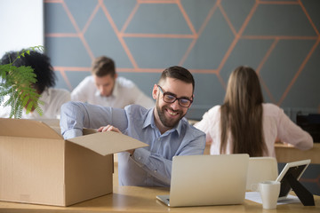 Smiling new male employee unpacking box with belongings at workplace, happy hired office worker newcomer on first working day concept, excited millennial businessman put laptop on desk in coworking
