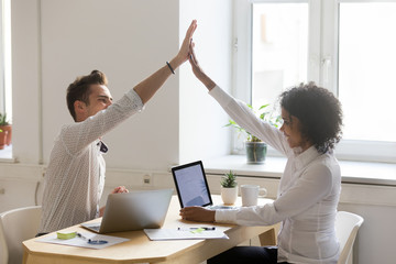 Happy african and caucasian colleagues giving high five celebrating good teamwork result or achievement in office, diverse motivated coworkers sharing business success, great collaboration concept