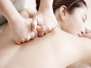 hands of masseuse performing massage on young asian woman