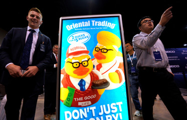 A shareholder walks by an image of Warren Buffett and Charlie Munger as rubber ducks at the Berkshire Hathaway Inc annual meeting, the largest in corporate America, in its hometown of Omaha